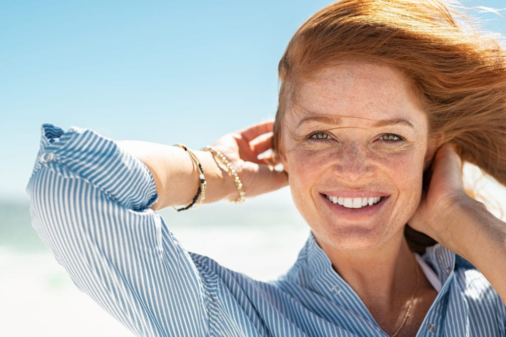 Woman with white smile posing on a beach
